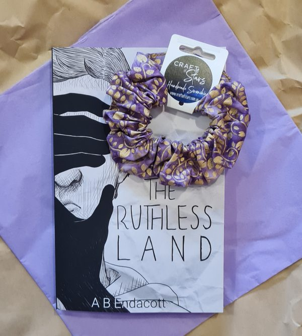 Ruthless Land book with purple and gold Craft of Stars scrunchie on a mauve background.